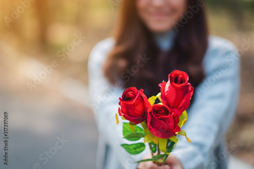 Closeup image of a beautiful asian woman holding and giving red roses flower on Canvas Print