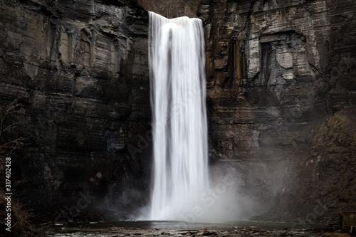 taughannock falls a silky smooth waterfall against a rock face cliff with splashing water at its base - 317402428