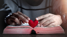 Hands And Red Heart In Bible On Wooden Table In Morning, Close Up, Love Of Christian Concept.