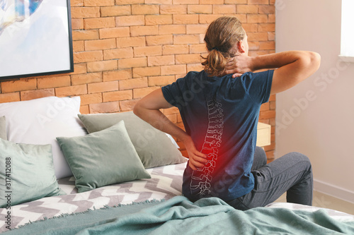 Fotomural Young man suffering from back pain at home