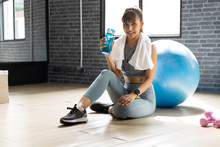 Young Woman Asian Drink Water After Workout In A Room With A Window With Natural Light. Fitness And Healthy Lifestyle Concept