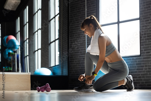 Fotomural Happy Young Asian Woman tying shoes Get ready to exercise at gym In a room with a window with natural light