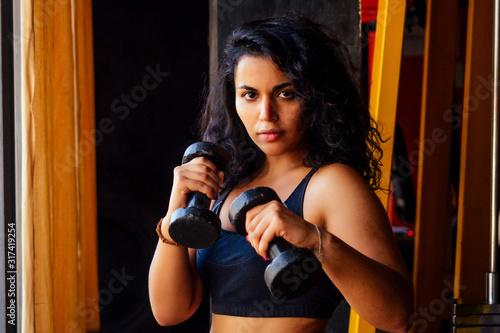 Photo hispanic latin curls hair american woman making direct hit with dumbbells