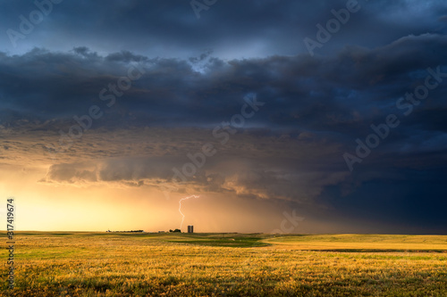 Vászonkép Stormy sky over a farm field at sunset