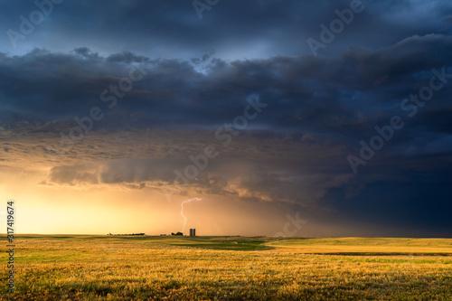 Obraz Stormy sky over a farm field at sunset - fototapety do salonu