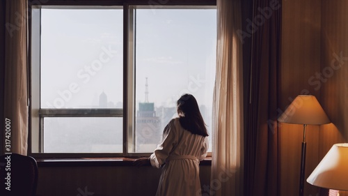 Asian women are staying in a hotel room on morning.Open the curtain and window in the room looking to outside view.Travel in holidays concept.Vintage tone.