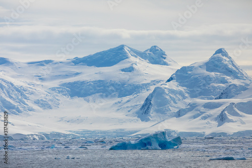 Fototapeta Snow and ice on the mountains near the water in Antarctica, a pristine remote landscape obraz