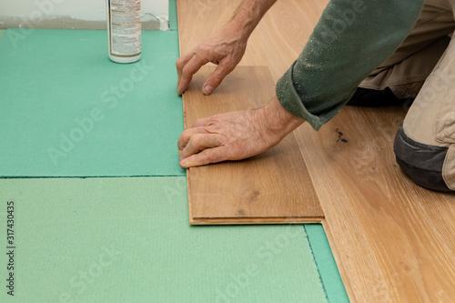 Man lays parquet floorand in the apartment. Fototapeta