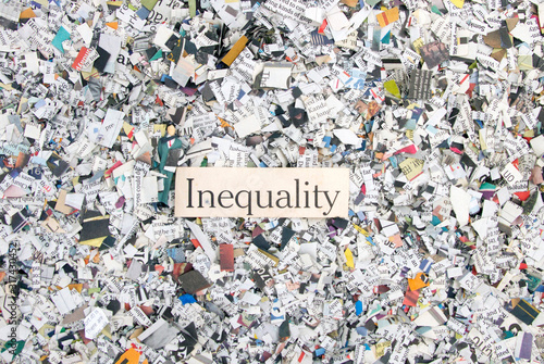 Fényképezés Newspaper confetti from above with the word Inequality