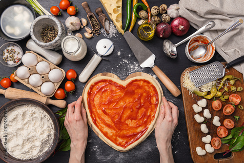 Fototapeta woman preparing a festive dinner for two in honor of Valentine's Day classic Italian pizza Margherita in the shape of a heart and mozzarella in the shape of a heart obraz