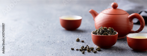 Green tea oolong in a clay tea cup bowl and tea pot. Stone background. Copy space.