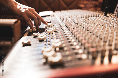 male professional sound engineer hand adjusting audio level on mixing console in Canvas Print