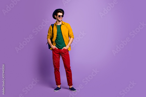 Obraz Full size photo of attractive gorgeous guy have spring walk holidays put hands in pockets wear blue bag velvet hat sunglass retro outfit isolated over purple color background - fototapety do salonu