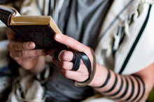 Reading Jewish Prayer And A Hand With Tefillin And Talit.
