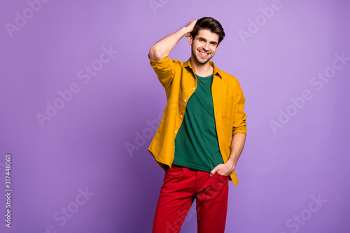 Photo of cheerful positive attractive handsome man smiling toothily in red pants isolated violet pastel color background combing his hair