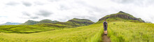 Man Hiking On A Small Trail With A Beautiful Panorama Of The Green Mountains Of Maloti Drakensberg Park, Rainbow Gorge Trail, South Africa
