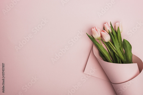 Fotografía top view of tulips wrapped in paper on pink background