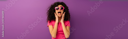 Fototapeta panoramic shot of scared bi-racial girl in sunglasses screaming on purple backgr
