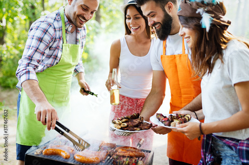 Obraz Group of happy friends having outdoor barbecue party and fun together - fototapety do salonu