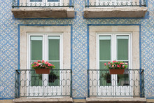 Historic House Facade With Blue Azulejos, Two Balconies And Geranium Flower Pots, Lisbon Portugal