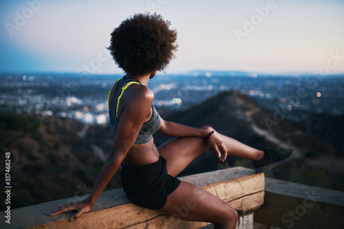 Fotomural fit african woman woman resting on bench at runyon canyon shortly after sunset