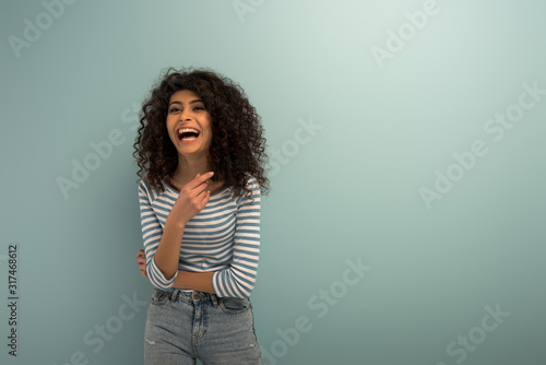 Fototapeta excited bi-racial girl laughing while pointing with finger on grey background obraz