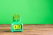 canvas print picture - Block calendar with the date of March 17 and a trefoil leaf on green background. St. Patrick's Day celebration concept.