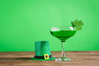 canvas print picture - Traditional drink green clover beer in glass with a clover leaf close-up. Cocktail for St. Patrick's Day celebration