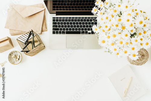 Cuadros en Lienzo Home office desk workspace with laptop, chamomile daisy flowers bouquet and notebook on white background