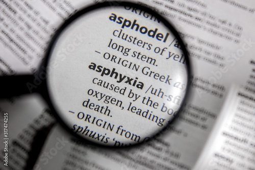 Photo The word or phrase asphyxia in a dictionary.