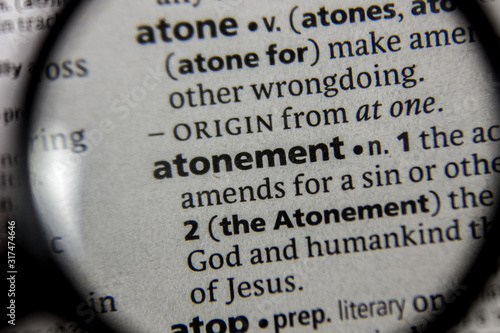 Photo The word or phrase atonement in a dictionary.