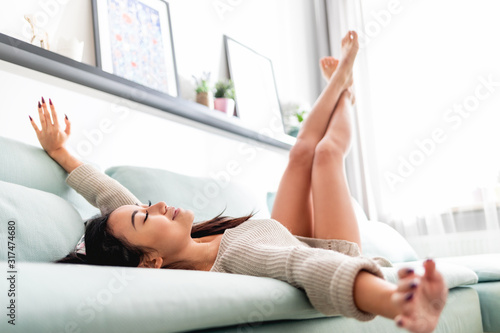 Leisure time at home, asian woman in positive mood relaxing on sofa Canvas Print