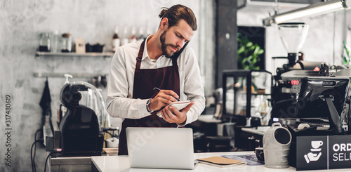 Photo Portrait of handsome bearded barista man small business owner working with lapto