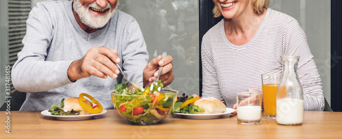 Senior couple enjoy eating  healthy breakfast together in the kitchen Fototapet