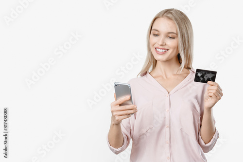 Fototapeta Smiling young lady isolated over white background using mobile phone holding credit card obraz