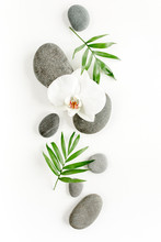 Spa Stones, Palm Leaves, Flower White Orchid And Zen Like Grey Stones On White Background. Flat Lay, Top View