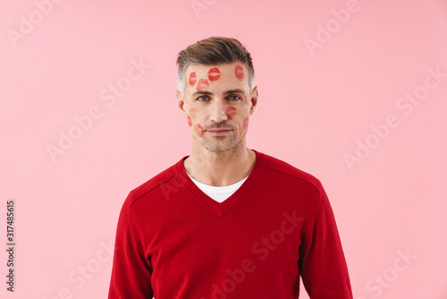 Portrait of handsome man with kiss marks at his face on valentines day