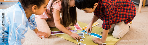 Panoramic shot of kids playing colorful game on floor in montessori school Wallpaper Mural