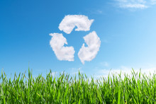 Clouds On The Blue Sky In Shape Of The Symbol Of Recycling On Green Background. Protection Nature And Future Concept.