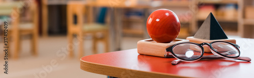 Valokuva Panoramic shot of educational game and eyeglasses on desk in montessori school
