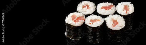 Fototapeta delicious sushi maki with tuna isolated on black, panoramic shot obraz