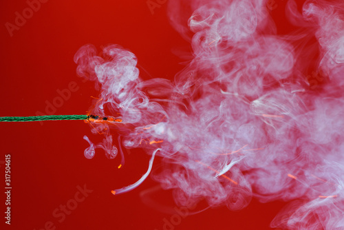 Burning fuse wick cord with sparks and smoke on red background Fototapet