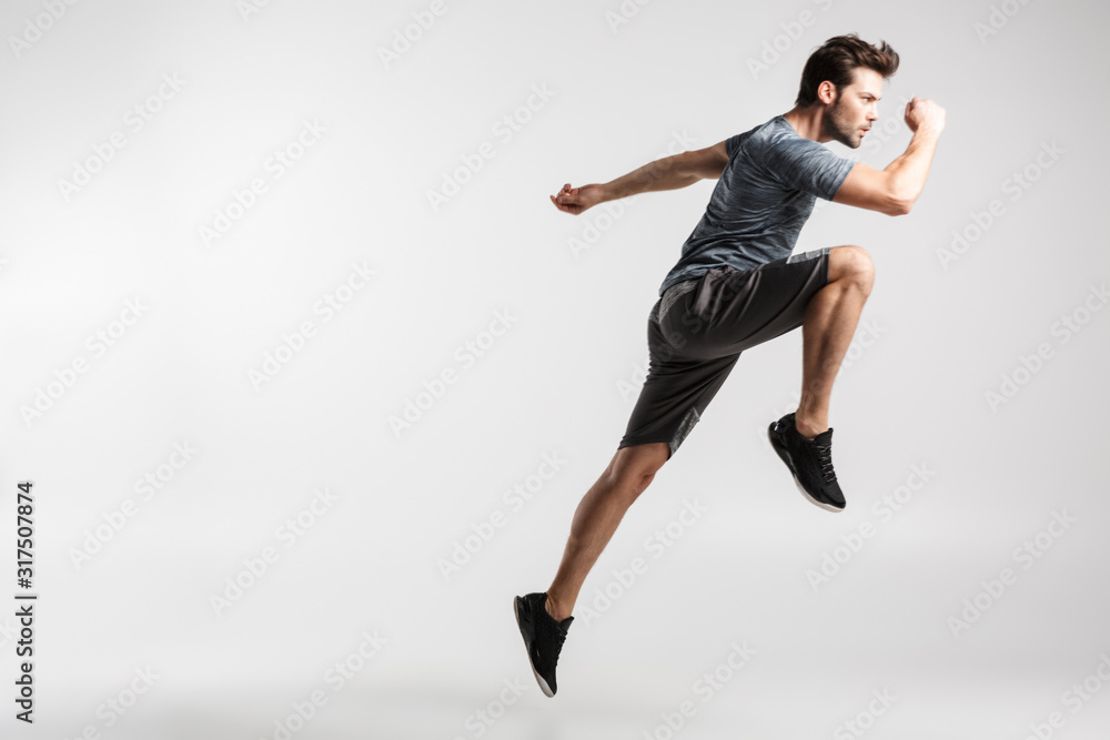 Fototapeta Image of young athletic man doing exercise while working out