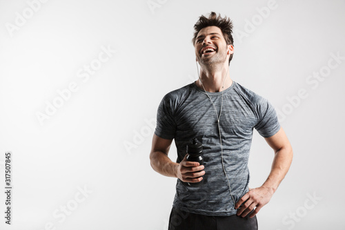 Fototapeta Image of young laughing man using earphones and holding water bottle obraz