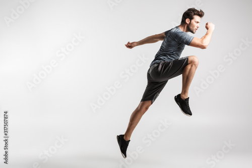 Fototapeta Image of young athletic man doing exercise while working out obraz