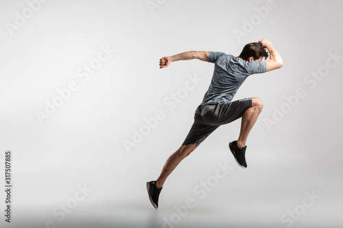 Image of young athletic man doing exercise while working out - 317507885