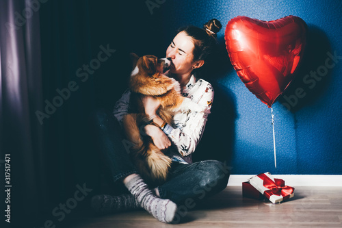 Photo A happy girl holding a small light puppy with a red ribbon