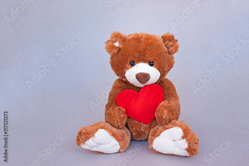 Valentines Teddy Bear holding wooden red heart #317521273