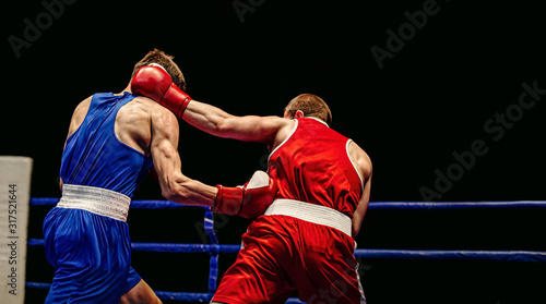 Photo boxing match in ring boxers exchange of blows