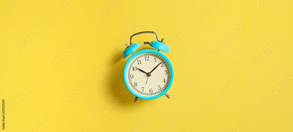 Fototapeta Turquoise vintage alarm clock on yellow background. Top view. Flat lay